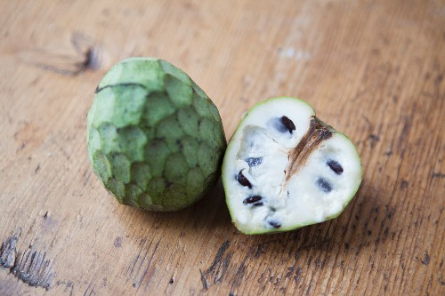 Whole and halved cherimoya on a wooden table