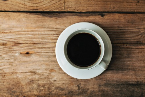 A cup of coffee on a wooden surface (seen from above)