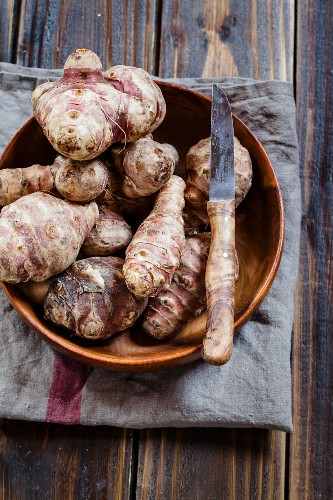 Jerusalem artichokes in a wooden bowl with a knife