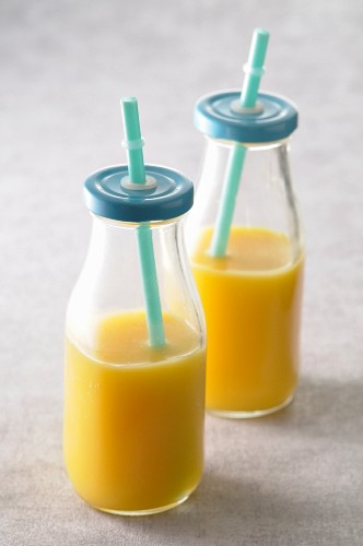 Orange juice in glass bottles with lids and straws
