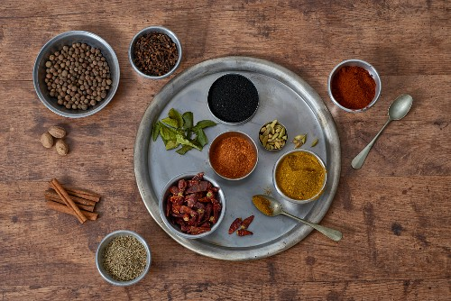Various Thai spices: red curry, yellow curry, Kafir lime leaves, cloves, anise, cinnamon, nutmeg, cardamom, chilli powder, dried chillis