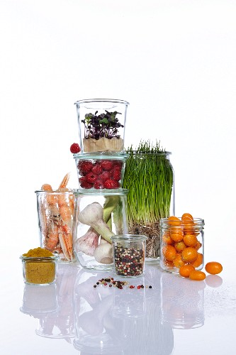Vegetables, fruit, herbs and prawns in glass containers