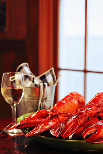 Cooked lobster and a glass of white wine on a windowsill (USA)
