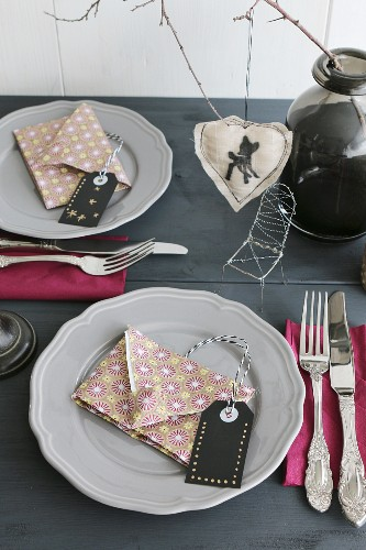 Table set for Christmas with napkins folded in shaped of envelopes and hand-crafted labels