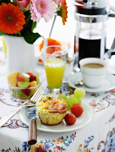 A breakfast table laid with fruit salad, juice, coffee and a savoury muffin