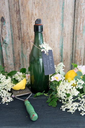 A bottle of elderflower syrup with lemons elderflowers and briar rose