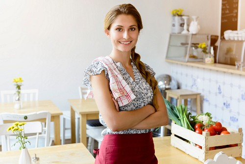 A young woman with an apron and a tea towel in a cafe