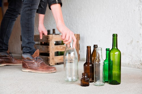A man placing empty bottles in a wooden crate