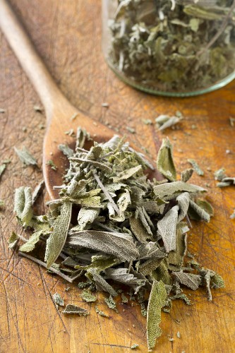Dried sage leaves on a wooden spoon