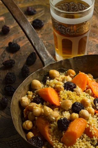 Vegan couscous with currants, chickpeas and carrots in a copper pan