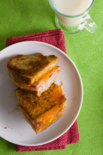 A grilled cheese sandwich with Canadian cheddar and back bacon with a glass of milk in the background