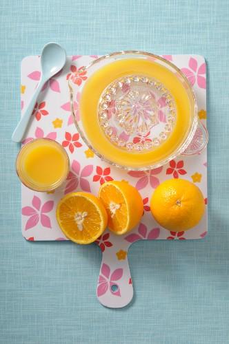 Freshly pressed orange juice, a juicer and oranges