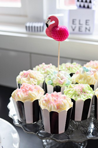 Cupcakes in black and white cases decorated with plastic flamingo