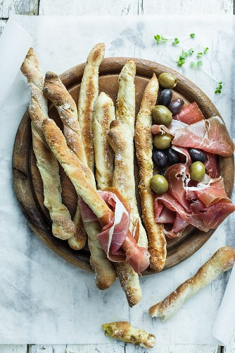 Grissini with ham and olives on a wooden board (seen from above)