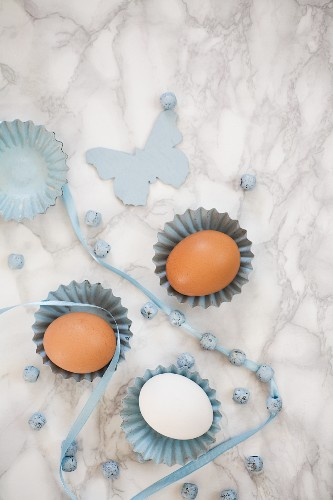 Hen's eggs in small baking tins with ribbon and beads on a marble surface