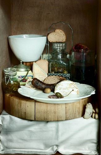 A vintage supper featuring sausage, cheese, papers and olives