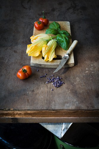 An arrangement of courgette flowers, tomatoes and basil on a chopping board