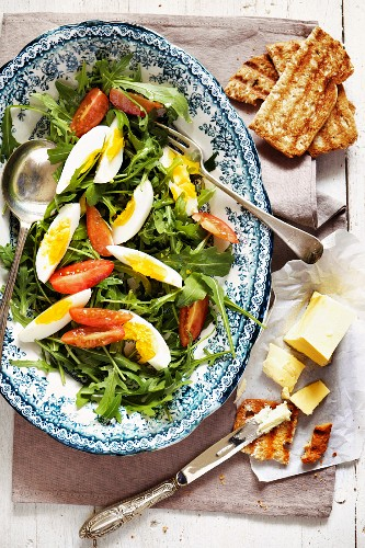 Rocket salad with egg and tomatoes served with toast and butter