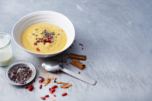 A bowl of mango smoothie with carrots, goji berries, cocoa nibs and cinnamon