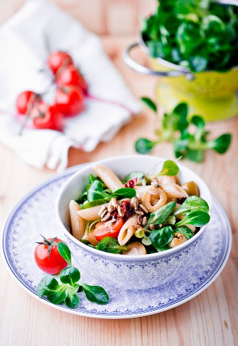 A salad with lambs lettuce, pasta, olives, tomatoes and pine nuts