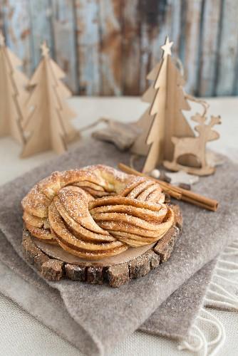 A cinnamon bun with icing sugar