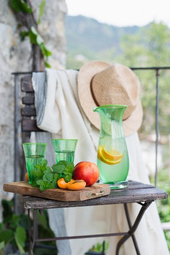 Fruit and lemonade on a wooden chair on a balcony (Italy)