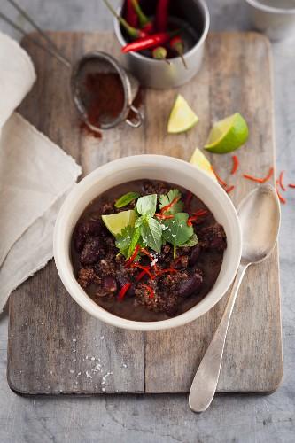 Chili Con Carne mit Kräutern auf Holzbrett