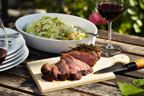 Grilled sirloin with a cabbage salad on a garden table