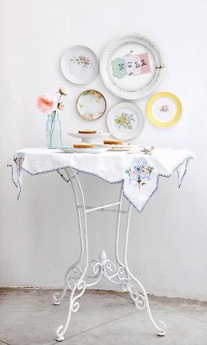 Weisser Tisch mit Käsekuchen und Teller an der Wand
