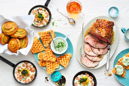 A brunch buffet with roast veal, waffles and fried eggs with shrimps