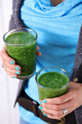 Glasses of spinach and cabbage smoothie with apple juice and chia seeds