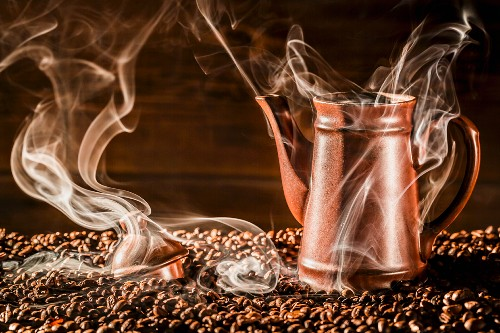 A jug of coffee on aromatic coffee beans