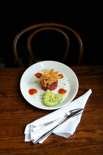 Tuna tartare with avocado on a rustic wooden table