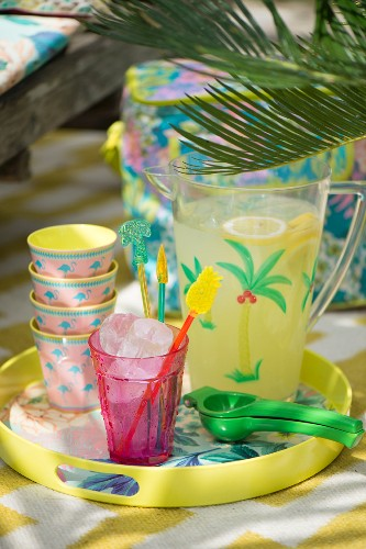 Colourful beakers and jug of refreshing drink on tray