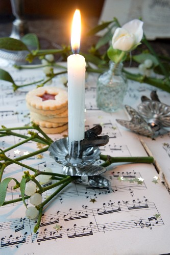 Burning candles on mistletoe sprigs with a stack of Christmas biscuits