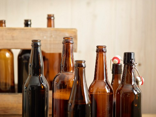 Open beer bottles in front of a wooden crate