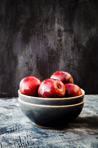 Red plums in a grey ceramic bowl