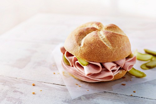 A roll with bologna and gherkins