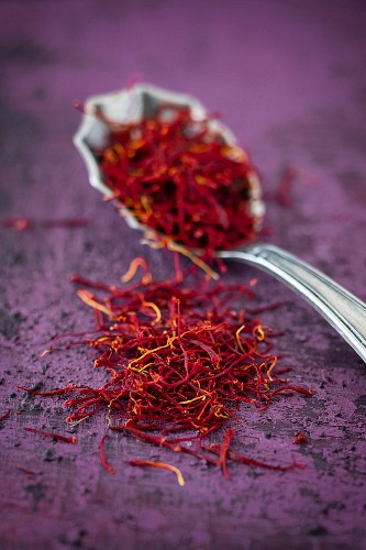 Saffron threads on a spoon and next to it