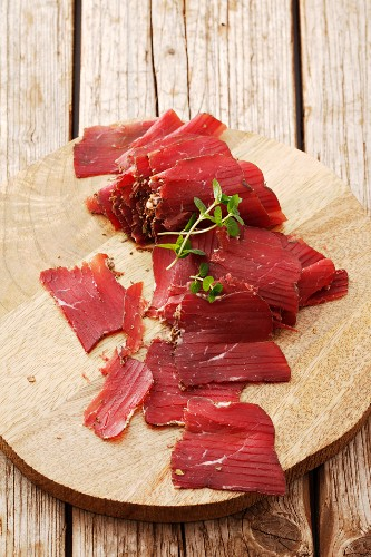 Sliced smoked beef on a wooden surface (South Tyrol)