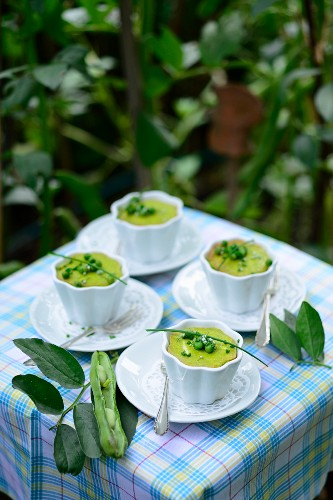 Pea flans with broad beans and chives on a table outside