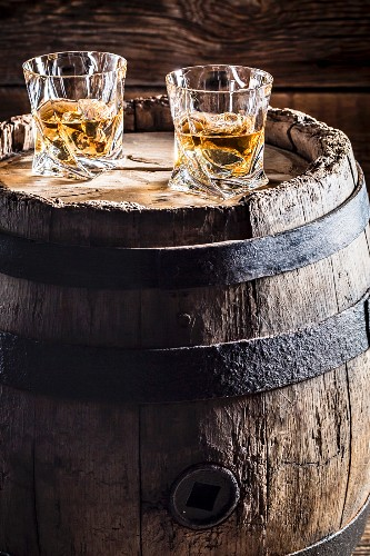 Two glasses of whisky with ice on an old wooden barrel