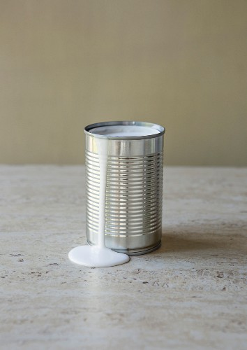 An opened tin of coconut milk