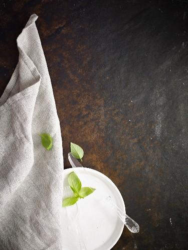 Glasbesteck auf weisser Porzellanschale mit Joghurt und Basilikumblättern