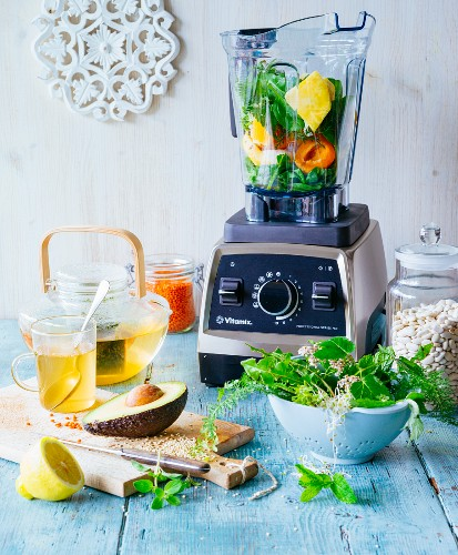 Ingredients for vegan fasting: a blender with fruit and vegetables, herb tea and herbs