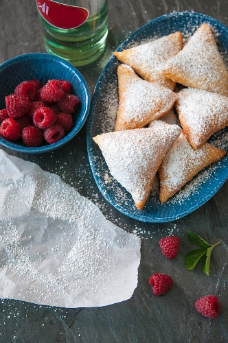 Beignets with icing sugar and raspberries