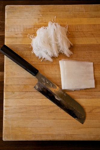 Finely sliced daikon radish Japanese style on a wooden chopping board with a Japanese knife