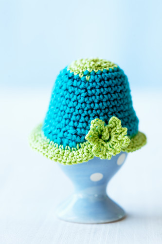 A crocheted egg cosy on top of an egg