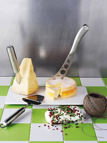 Various sorts of cheese, a cheese knife, a cheese slicer and kitchen twine