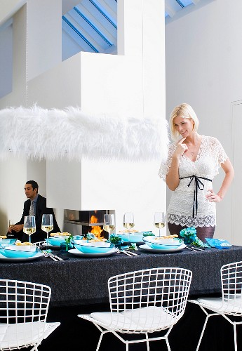 A blonde woman looking at a table laid for Christmas dinner